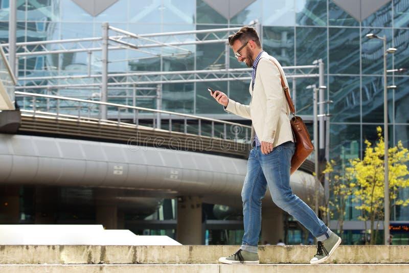 Hombre caucásico feliz que camina al aire libre y que lee el mensaje de texto foto de archivo libre de regalías