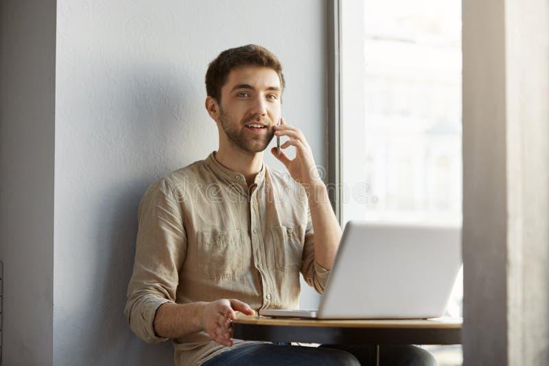 Hombre caucásico hermoso con sonrisas del pelo oscuro, sentándose en cafetería con el ordenador portátil, hablando en el teléfono fotografía de archivo