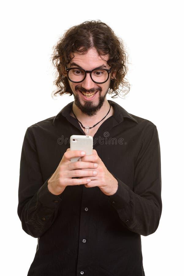 Hombre caucásico hermoso feliz que ríe mientras que usando el teléfono móvil foto de archivo