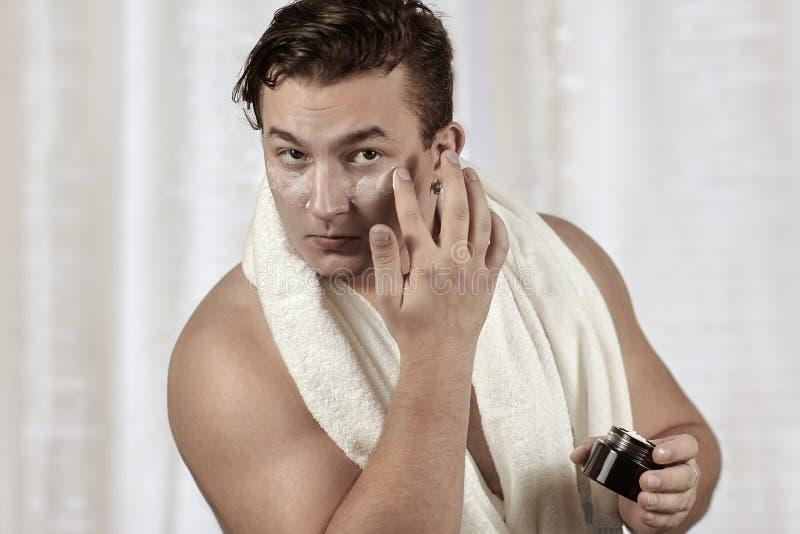 Hombre caucásico hermoso joven que aplica la crema debajo de los ojos, toalla en hombros Cara que cuida, rutina diaria del metros foto de archivo
