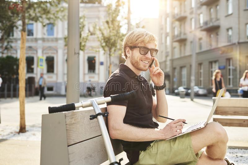Hombre caucásico hermoso que usa sentarse del ordenador portátil al aire libre en un parque Día de la sol del verano Concepto de  imagen de archivo
