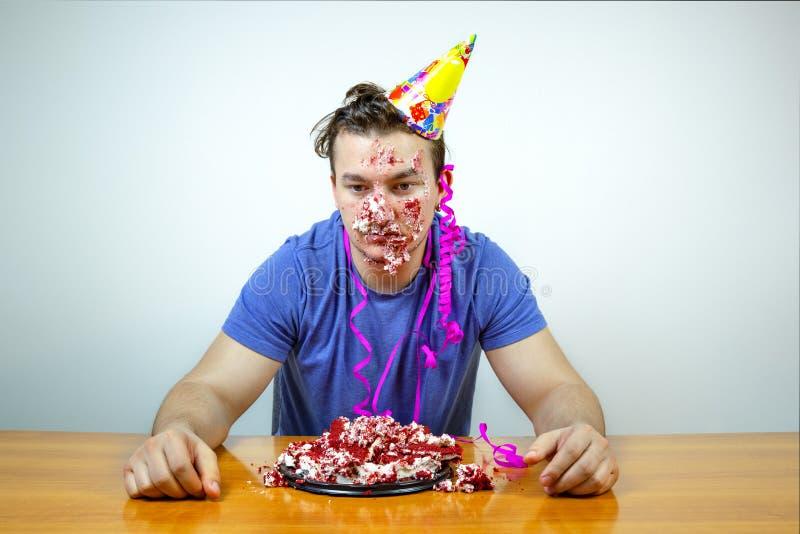 Hombre caucásico infeliz descontentado con el sombrero del cono en la cabeza y arrugar la torta que mira abajo con la expresión d imágenes de archivo libres de regalías