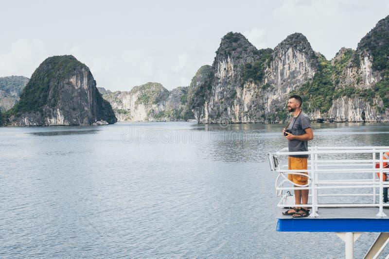 Hombre caucásico joven con una situación de la cámara en una cubierta del transbordador que pasa por alto la bahía de Halong, Vie fotos de archivo