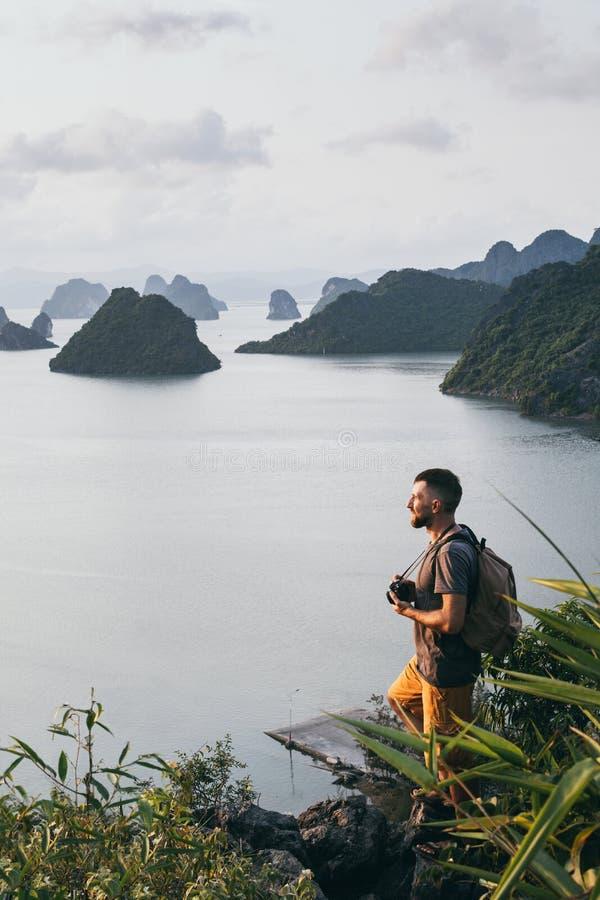 Hombre caucásico joven con una situación de la cámara en un acantilado que pasa por alto la bahía durante puesta del sol, Vietnam fotografía de archivo
