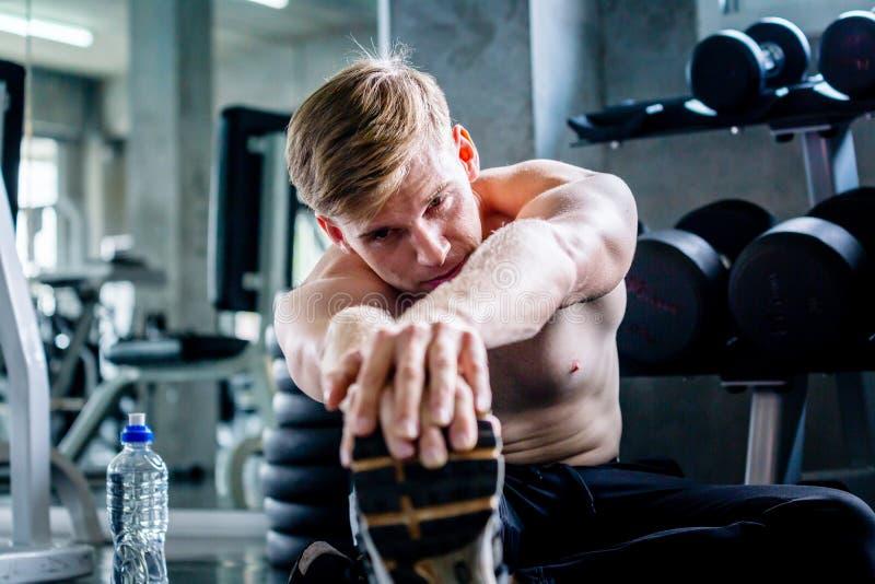 Hombre caucásico joven en un gimnasio, estirando el cuerpo con dolor en piso imagen de archivo