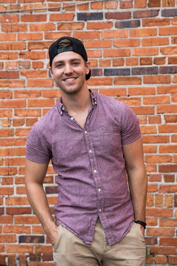 Hombre caucásico joven hermoso con el teléfono móvil y al revés el sombrero que sonríe para los retratos delante del exterior tex imagenes de archivo