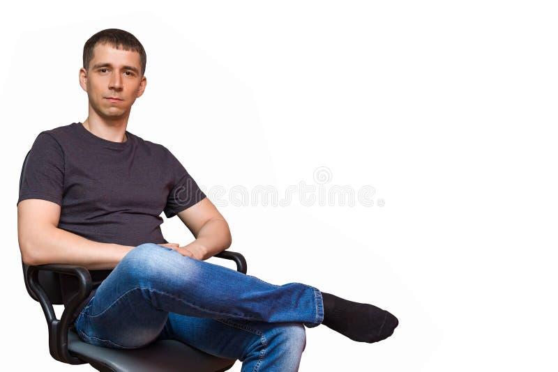 Hombre caucásico joven positivo, sentándose en una silla que pone a sus FO foto de archivo