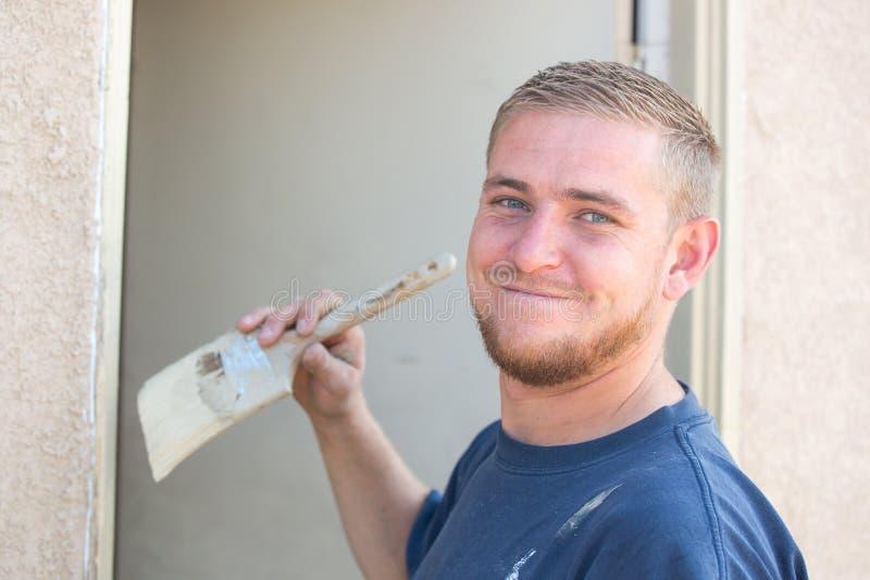 Hombre caucásico joven que sonríe como él está pintando la casa imagen de archivo libre de regalías
