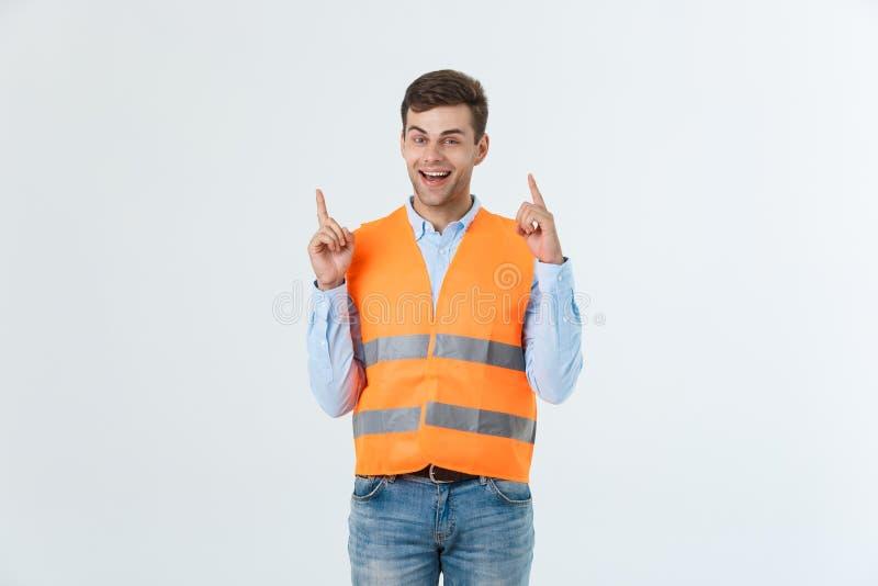 Hombre caucásico joven sobre el uniforme del contratista del fondo que lleva blanco y casco de seguridad sorprendidos con una ide fotografía de archivo libre de regalías