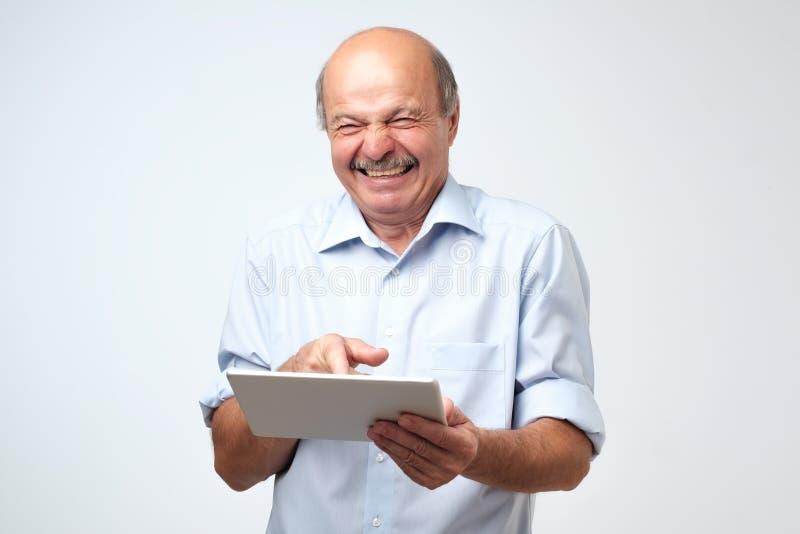 Hombre caucásico maduro del ganador eufórico que ríe con una tableta Él vio el vídeo o la broma muy divertido foto de archivo