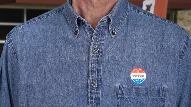 Hombre caucásico mayor en ropas de trabajo con la etiqueta engomada votada imagen de archivo libre de regalías