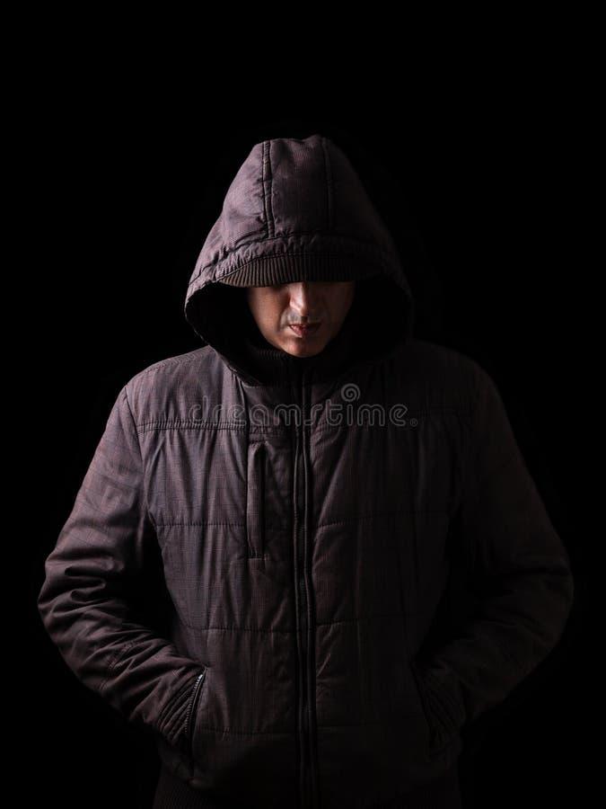 Hombre caucásico o blanco asustadizo y espeluznante que oculta en las sombras foto de archivo