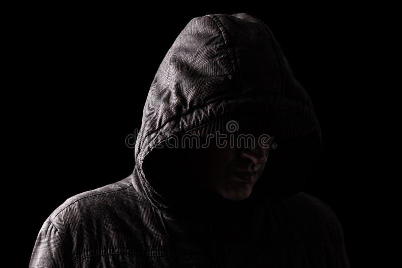 Hombre caucásico o blanco asustadizo y espeluznante que oculta en las sombras imagenes de archivo