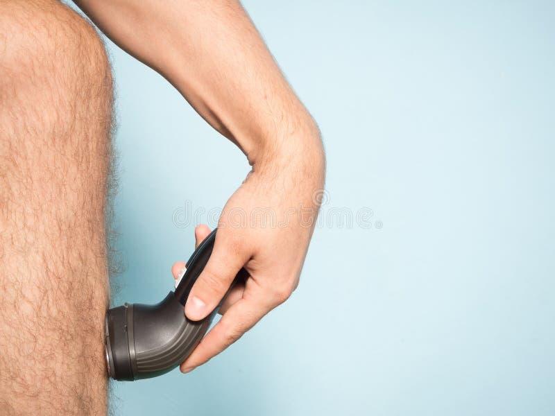 Hombre caucásico que afeita el pelo de las piernas fotografía de archivo