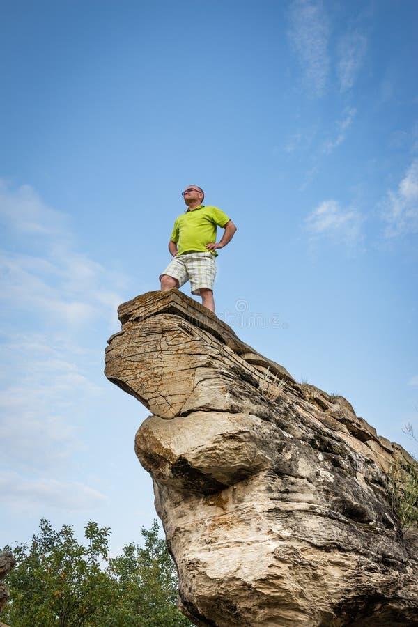 Hombre caucásico que se coloca en la extremidad de una alta formación de roca natural de la piedra arenisca fotos de archivo libres de regalías