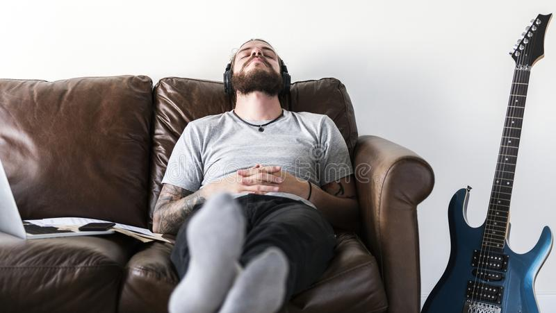 Hombre caucásico que toma una rotura del trabajo escuchando el concepto del alivio de tensión de la música imagen de archivo