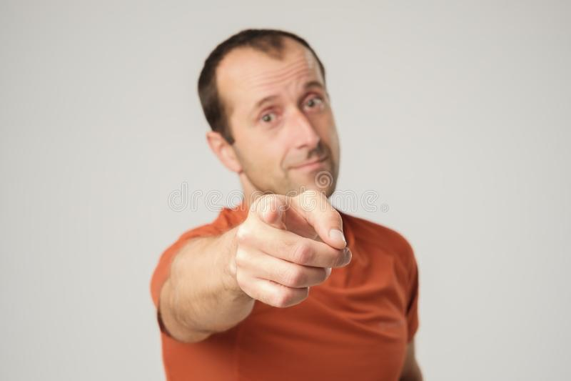 Hombre caucásico sonriente en camiseta anaranjada que señala el finger en usted fotos de archivo