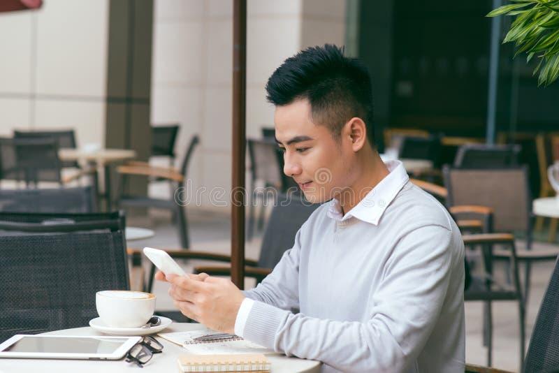 Hombre cauc?sico joven hermoso que se sienta en el caf? usando el tel?fono m?vil y que come caf? Var?n asi?tico con la taza de ca foto de archivo libre de regalías