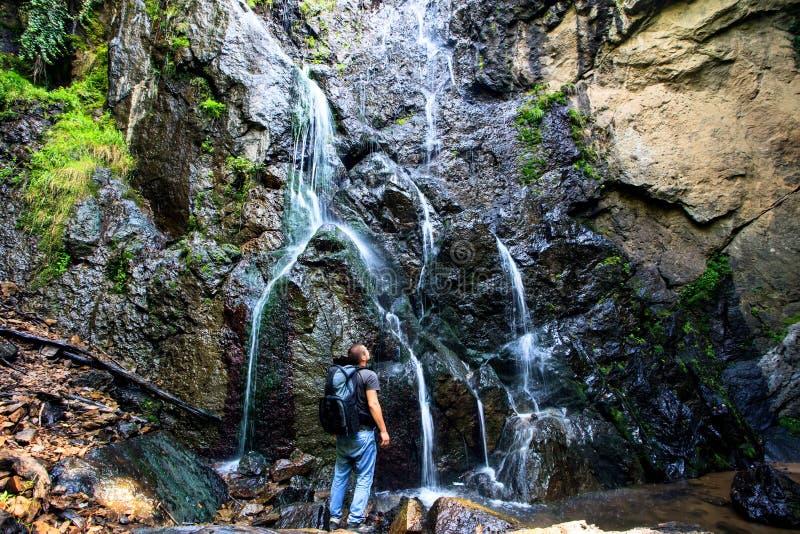 Hombre cerca de la cascada foto de archivo