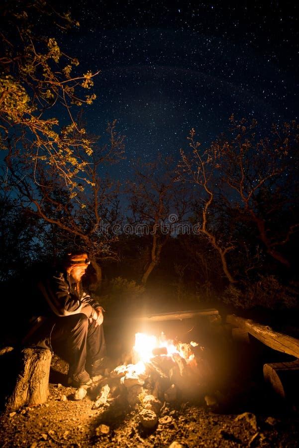 Hombre cerca de la hoguera ardiente en la noche debajo de un cielo estrellado imagen de archivo