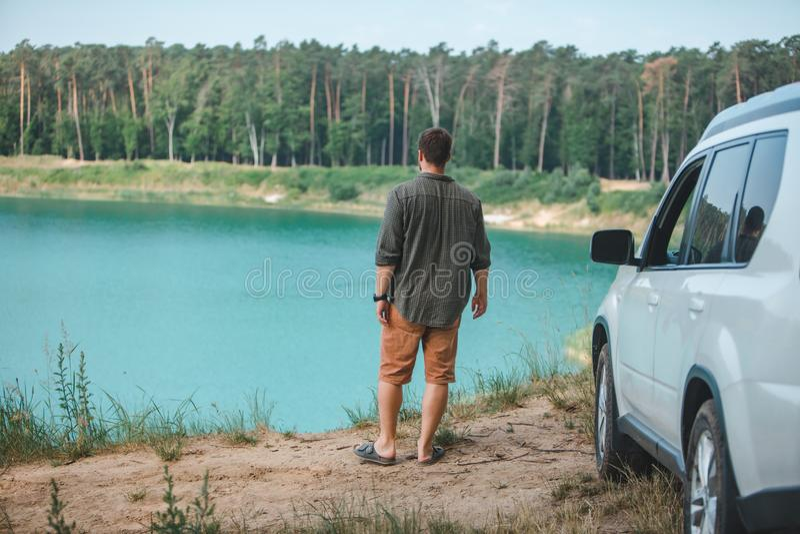 Hombre cerca del coche blanco del suv en el borde que mira el lago con agua azul foto de archivo libre de regalías