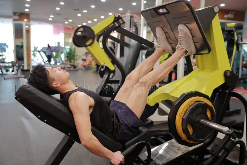 Hombre chino asiático en el entrenamiento del hombre del deporte de ŒFitness del ¼ del ï del gimnasio de la fuerza de la pierna e foto de archivo libre de regalías