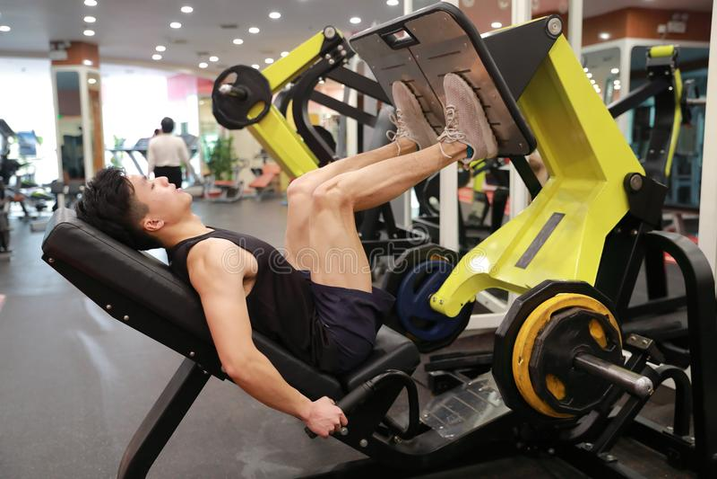Hombre chino asiático en el entrenamiento del hombre del deporte de ŒFitness del ¼ del ï del gimnasio de la fuerza de la pierna e fotos de archivo libres de regalías