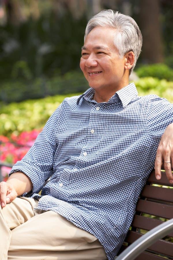 Hombre chino mayor que se relaja en banco de parque fotografía de archivo