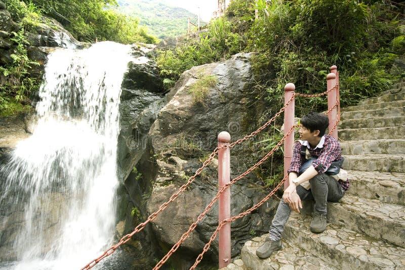 Hombre chino que se sienta en la escalera foto de archivo