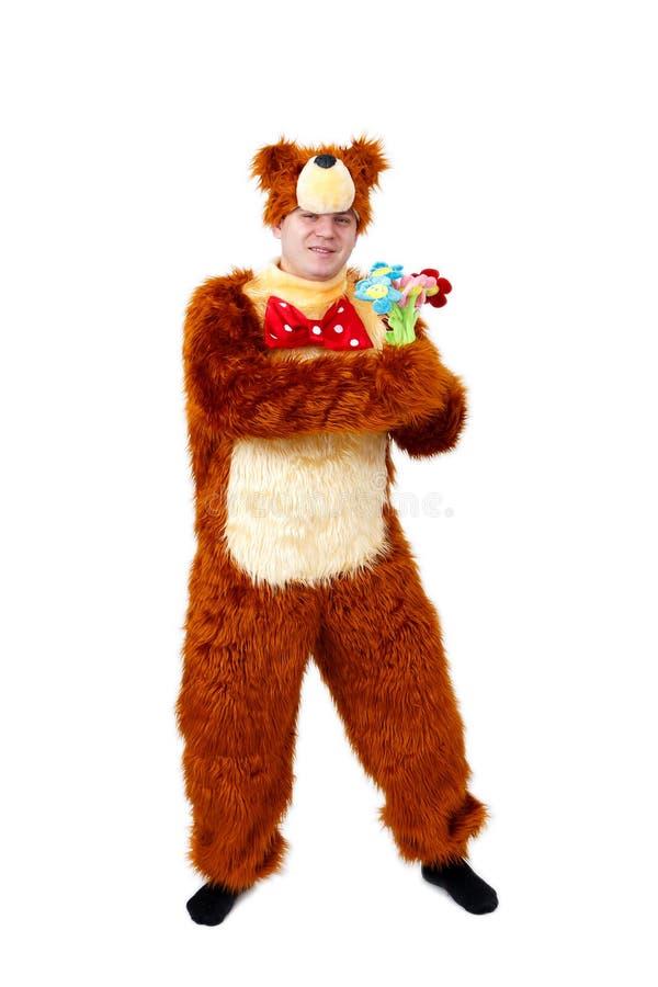 Hombre chistoso en traje del oso con las flores del juguete aisladas en blanco fotos de archivo