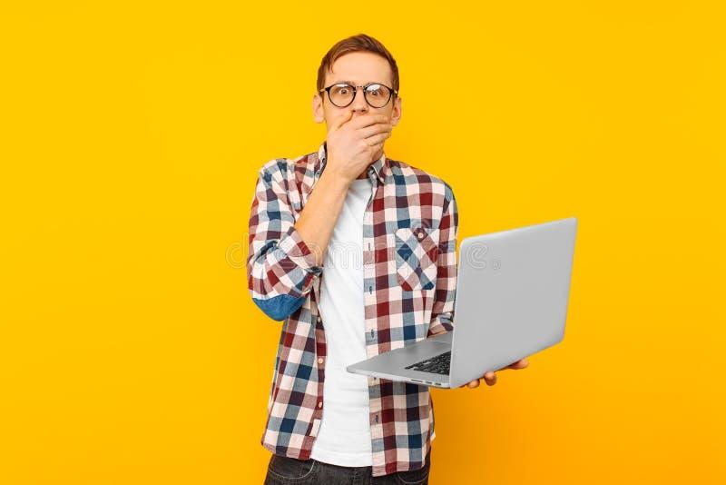 Hombre chocado con el ordenador portátil, en fondo amarillo, hombre que hace compras en línea imagen de archivo