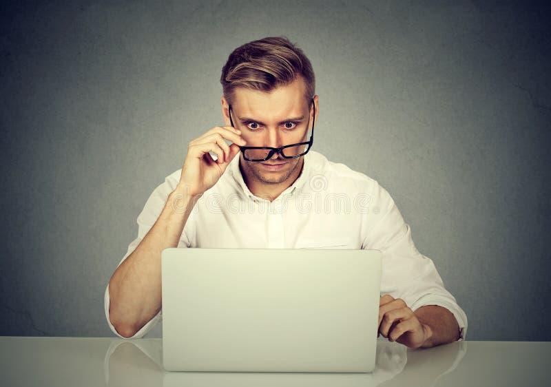 Hombre chocado confuso que mira su ordenador portátil foto de archivo libre de regalías