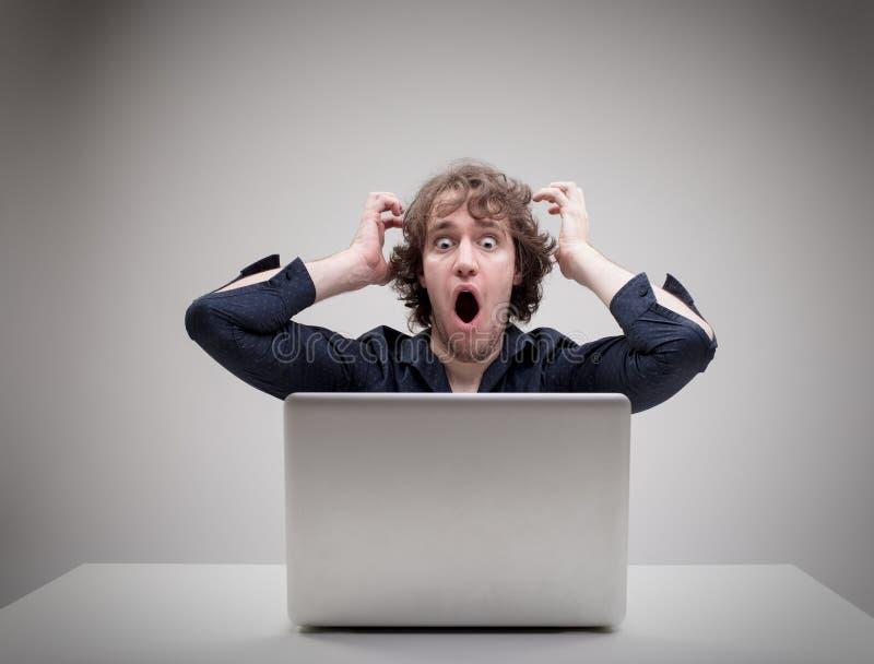 Hombre chocado delante de su ordenador fotos de archivo libres de regalías