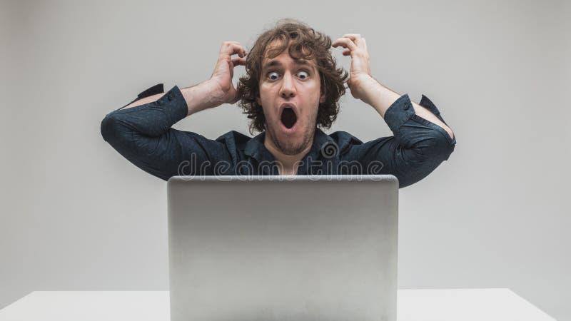 Hombre chocado delante de su ordenador fotografía de archivo libre de regalías