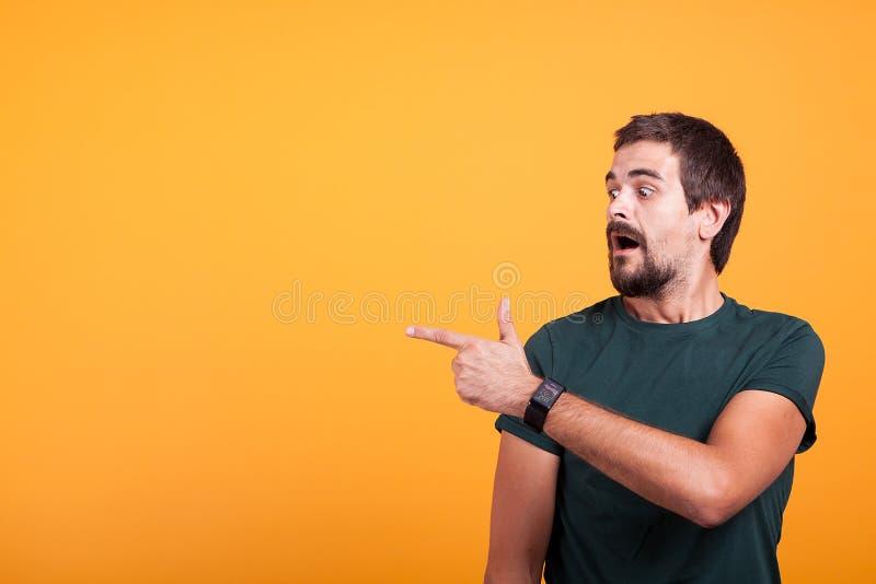 Hombre chocado expresivo que señala en su derecha con su boca abierta foto de archivo