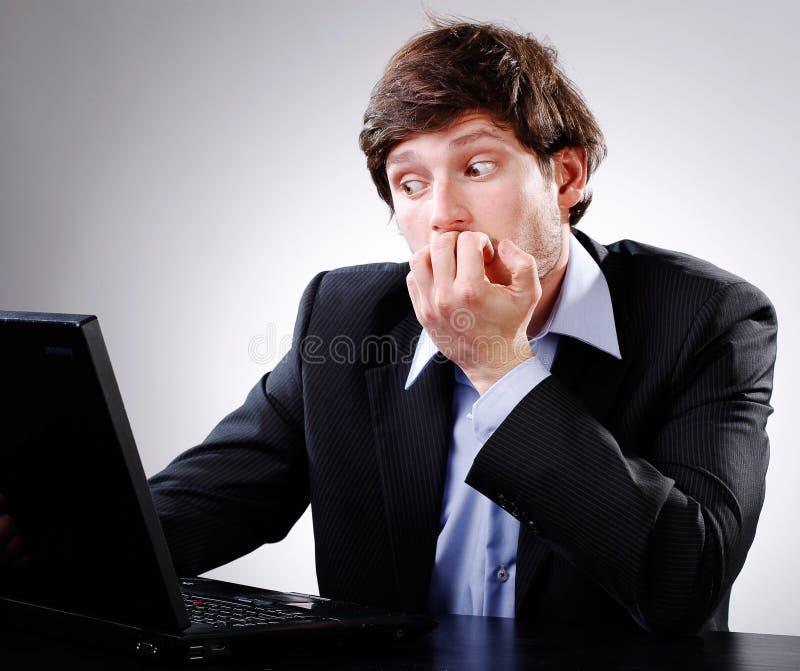 Hombre chocado mirando el ordenador foto de archivo