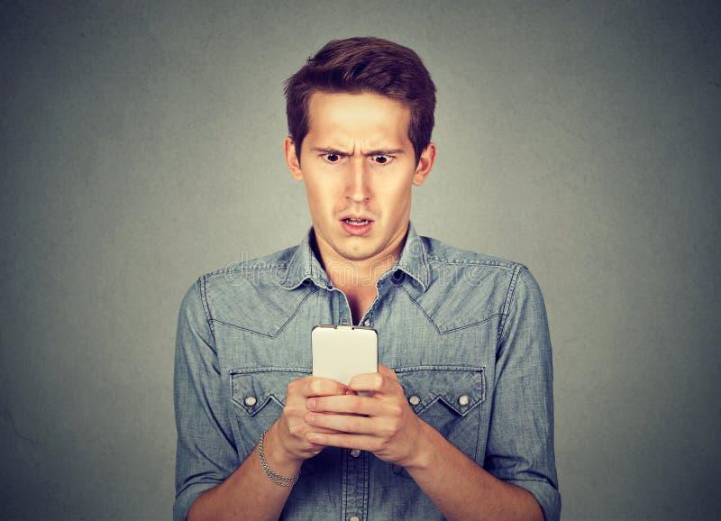 Hombre chocado que comprueba el teléfono móvil fotografía de archivo