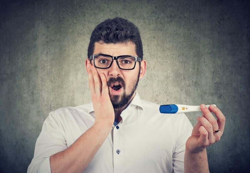 Hombre chocado que lleva a cabo una prueba positiva de la paternidad o de embarazo imagen de archivo