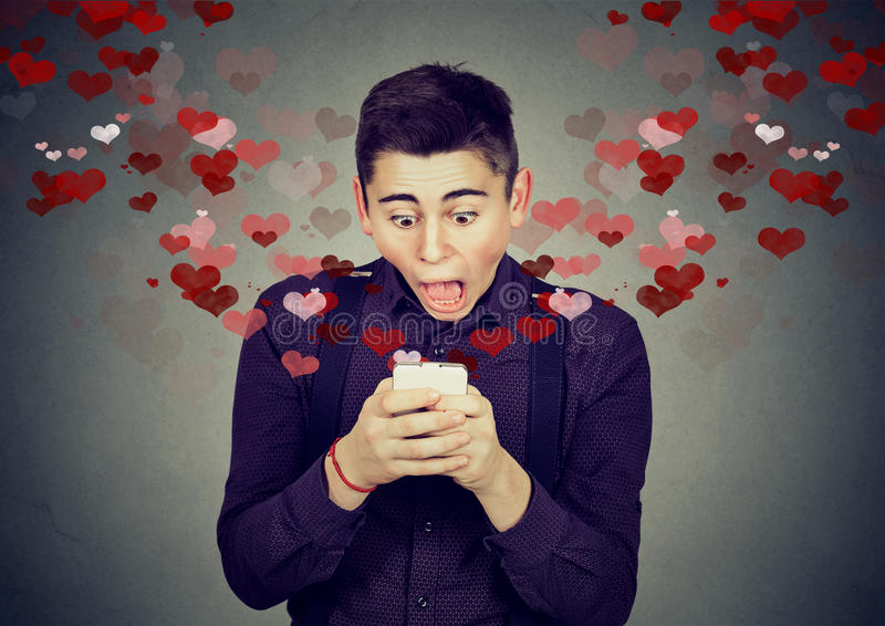 Hombre chocado que recibe el mensaje de texto del SMS del amor en el teléfono móvil imagen de archivo