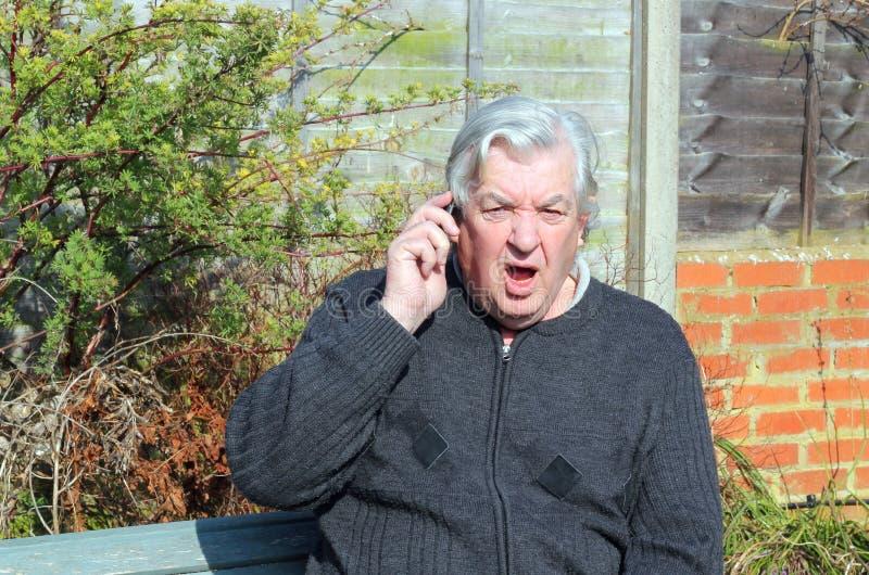 Hombre chocado que usa el teléfono móvil. fotografía de archivo