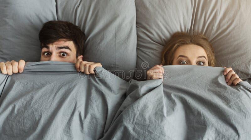 Hombre chocado y mujer que ocultan debajo de la manta en su cama en casa fotografía de archivo