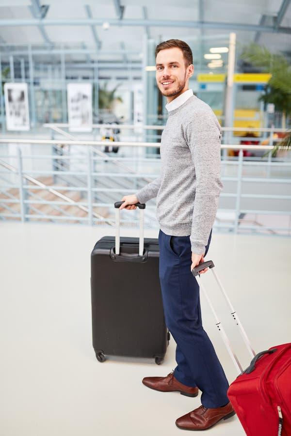 Hombre como pasajero con la carretilla en el camino en el terminal imagen de archivo libre de regalías