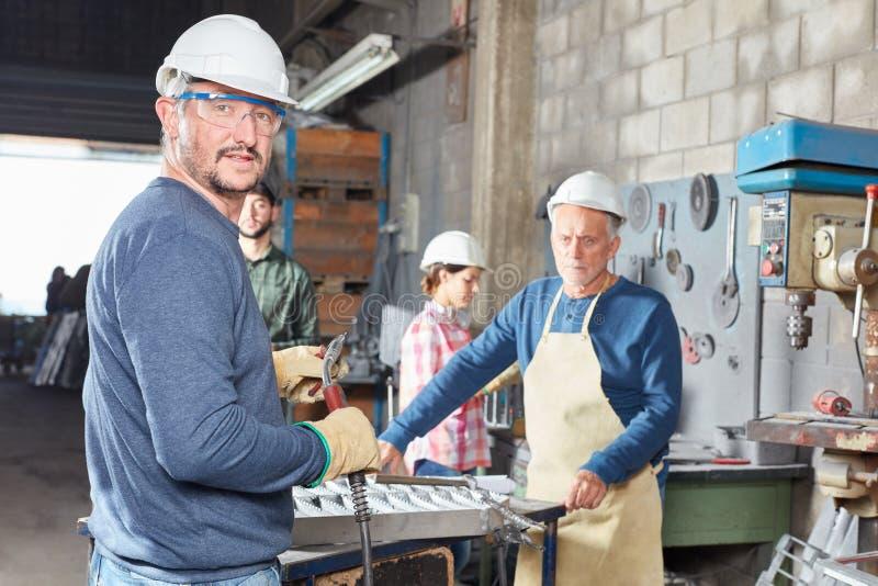 Hombre como trabajador de cuello azul con la soldadora imagen de archivo