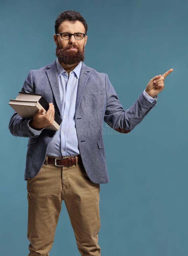 Hombre con barba sosteniendo libros y señalando fotos de archivo