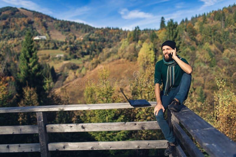 Hombre con barba y portátil sentado en el pasamanos y habla por teléfono Hipster independiente de vacaciones en las montañas foto de archivo libre de regalías