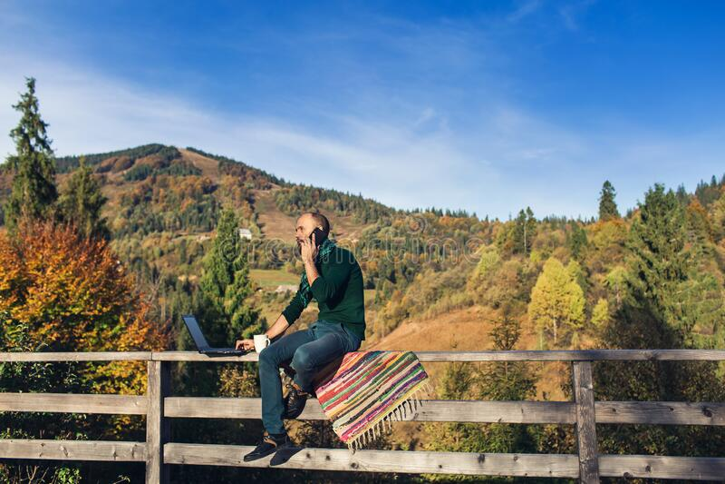 Hombre con barba y portátil sentado en el pasamanos y habla por teléfono Hipster independiente de vacaciones en las montañas imágenes de archivo libres de regalías