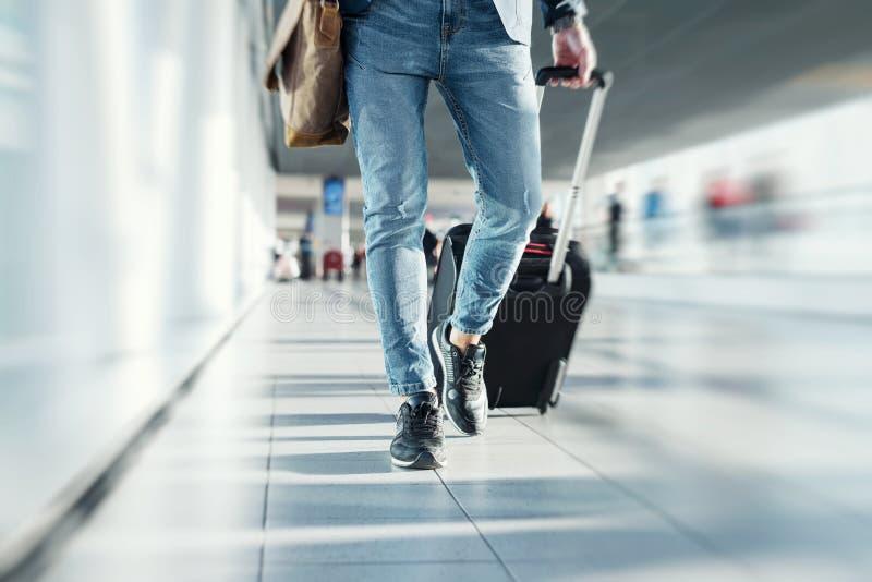 Hombre con bulto de mano que camina en aeropuerto imágenes de archivo libres de regalías