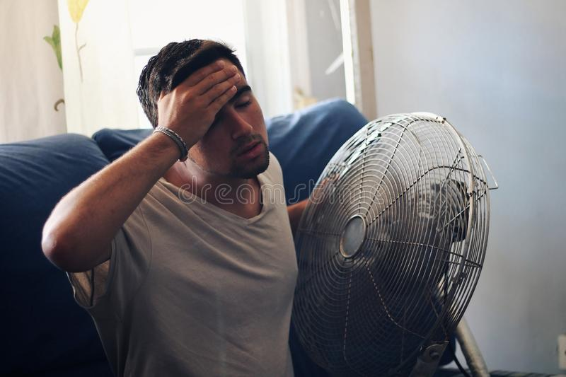Hombre con calor y una puerta siguiente de la fan foto de archivo libre de regalías