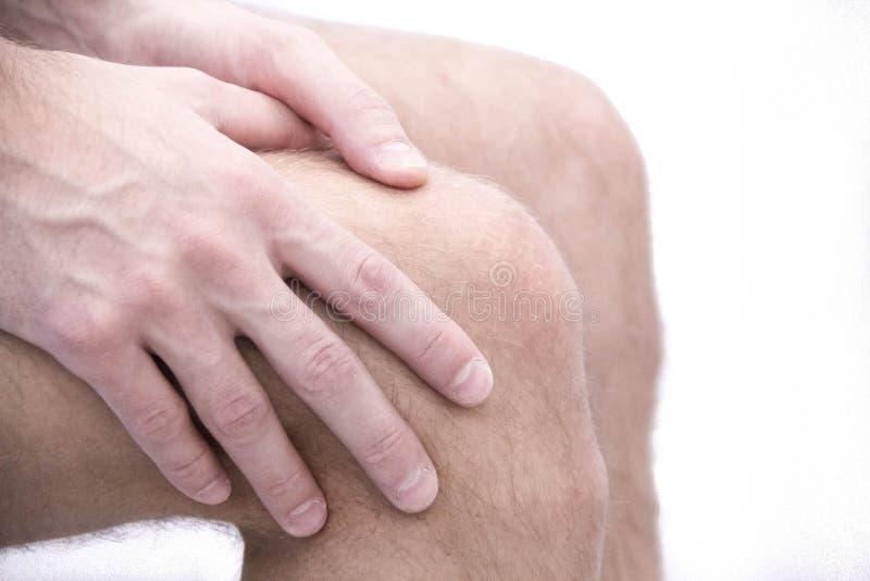 Hombre con dolor de la rodilla y el sentirse mal en oficina médica dolor común de la osteoartritis después del deporte Roturas y  imagen de archivo