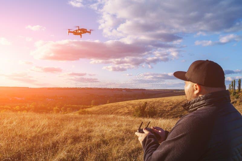 Hombre con el abejón de funcionamiento del vuelo del control remoto o helicóptero del patio - pequeño avión moderno para la fabri imágenes de archivo libres de regalías
